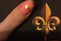 A picture of my thumb with a fleur de lis sticker, next to the fleur de lis on the back of the book