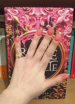 A photo of my hand held up in front of Belle Revolte; my nails have a French manicure look with a pink base & a gold tip with glitter!